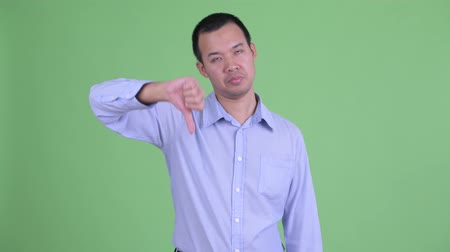 pas d accord : Studio shot of sad Asian businessman giving thumbs down Vidéos Libres De Droits