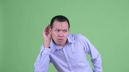 pletyka : stressed Asian businessman listening and looking shocked