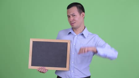 pas d accord : Stressed Asian businessman holding blackboard and giving thumbs down