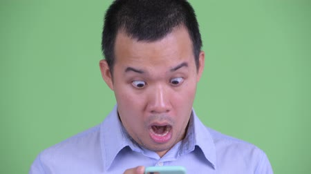 в середине : Face of happy Asian businessman using phone and looking surprised