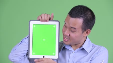 capelli corti : Face of happy Asian businessman talking while showing digital tablet