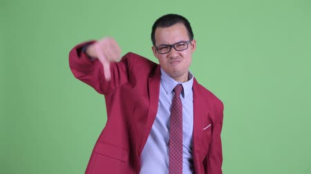 pouce vers le bas : Angry Asian businessman with eyeglasses giving thumbs down