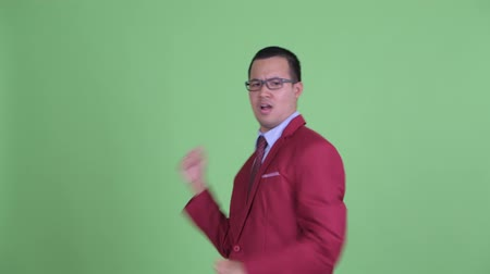 アクションショット : Happy Asian businessman with eyeglasses dancing