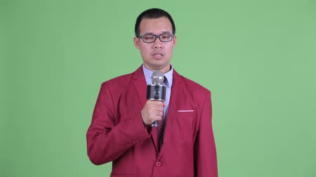 gergin : Nervous Asian businessman with eyeglasses using microphone Stok Video