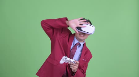 контроллер : Asian businessman in suit using virtual reality headset and playing games