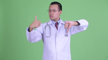 vélemény : Confused Asian man doctor with eyeglasses choosing between thumbs up and thumbs down
