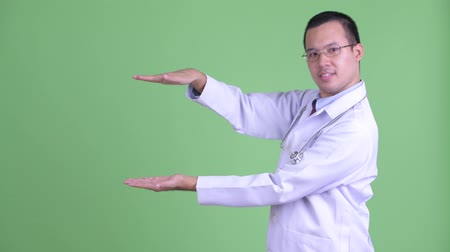 güneydoğu : Happy Asian man doctor snapping fingers and showing something Stok Video