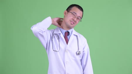 ferido : Stressed Asian man doctor with eyeglasses having neck pain