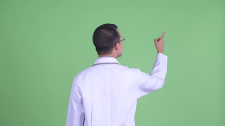 direkt : Rear view of Asian man doctor with eyeglasses pointing finger Stok Video