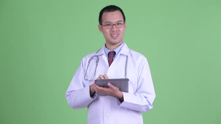 átnyújtás : Happy Asian man doctor talking while using digital tablet