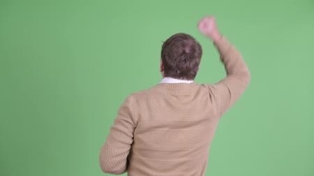 raising fist : Rear view of happy overweight bearded man with fists raised