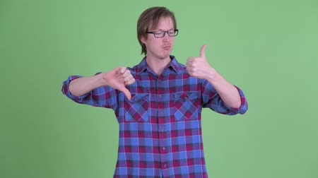fikirler : Confused young hipster man choosing between thumbs up and thumbs down Stok Video