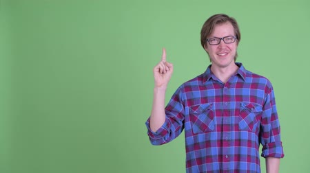 reminder : Happy young handsome hipster man pointing up