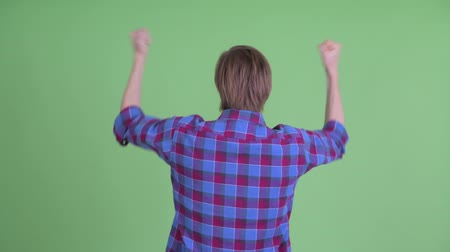 raising fist : Rear view of happy young hipster man with fists raised