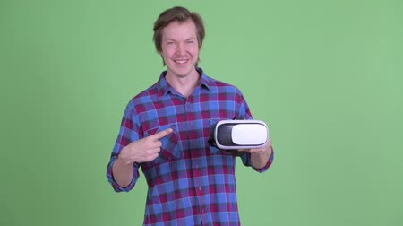 simulace : Happy young hipster man holding and pointing at virtual reality headset