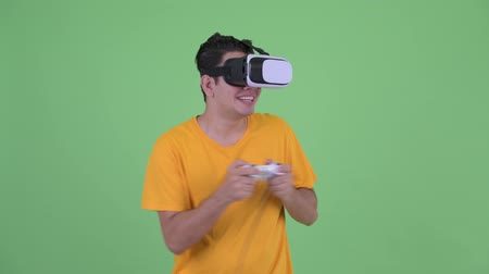 videogame screen : Happy young multi ethnic man playing games while using virtual reality headset