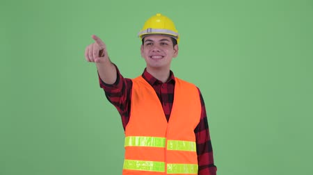 direkt : Happy young multi ethnic man construction worker directing and pointing finger Stok Video