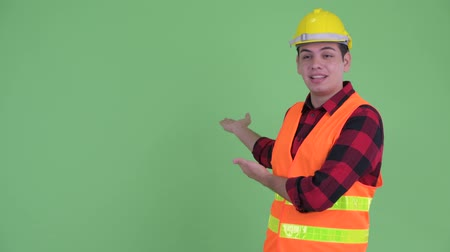 átnyújtás : Happy young multi ethnic man construction worker presenting to the back