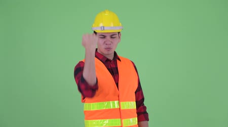 torcendo : Happy young multi ethnic man construction worker with fist raised Stock Footage