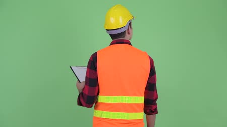 looking far away : Rear view of young multi ethnic man construction worker holding clipboard