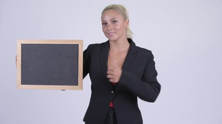 schválení : Young happy blonde businesswoman holding blackboard and giving thumbs up