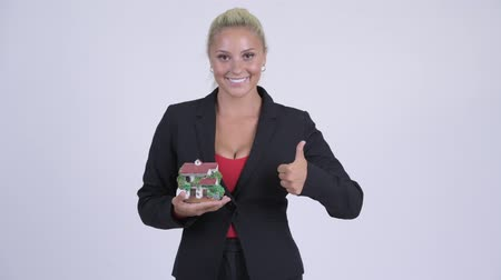 figurka : Young happy blonde businesswoman holding house figurine and giving thumbs up