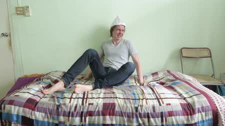 elmélet : Stressed young man wearing tin foil hat and getting scared in the bedroom