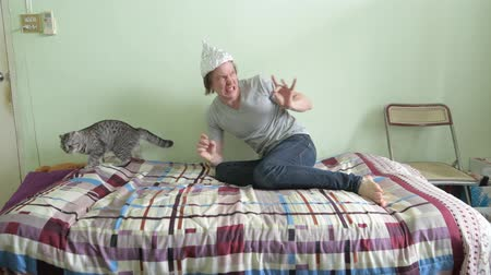 complot : Scared young man wearing tin foil hat and panicking with cat in the bedroom