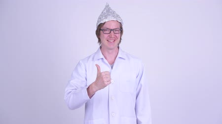 complot : Happy young man doctor with tinfoil hat giving thumbs up Vidéos Libres De Droits