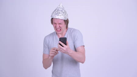 pánik : Stressed young man with tinfoil hat using phone and looking scared