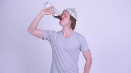 cola : Young man with tinfoil hat drinking bottle of soda Stock Footage