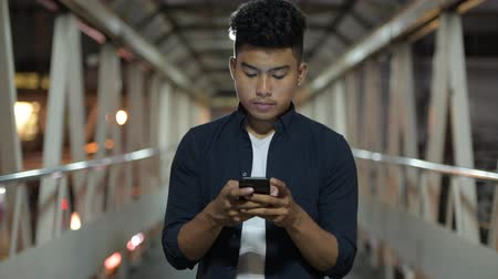 mianmar : Happy young Asian man using phone on the footbridge at night