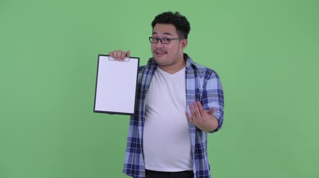 check list : Happy young overweight Asian hipster man showing clipboard and giving thumbs up