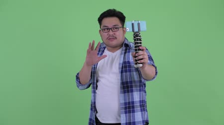 tripod shot : Happy young overweight Asian hipster man vlogging and showing phone Stock Footage