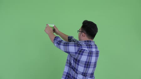 túlsúly : Rear view of young overweight Asian hipster man taking picture with phone