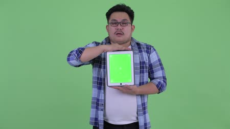 slecht nieuws : Stressed young overweight Asian hipster man showing digital tablet