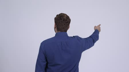 Rear view of young Indian businessman pointing finger Wideo