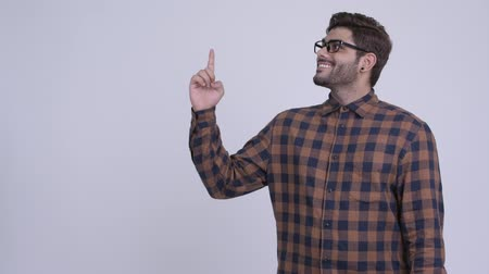 Happy young bearded Indian hipster man thinking while pointing up