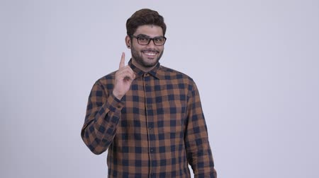 Happy young bearded Indian hipster man pointing up Dostupné videozáznamy