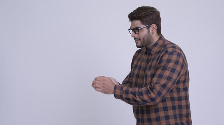 Happy young bearded Indian hipster man snapping fingers and showing something