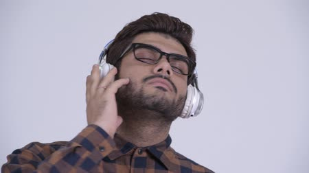 Young bearded Indian hipster man listening to music