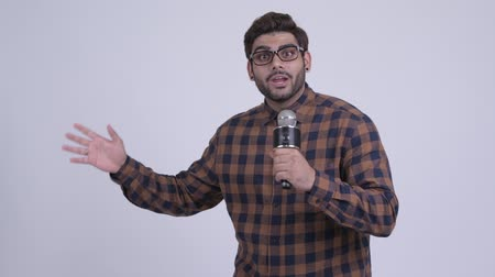 Happy young bearded Indian hipster man presenting something with microphone Wideo