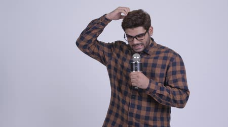 microphone : Young bearded Indian hipster man as host making mistake
