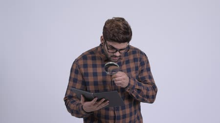 Young bearded Indian hipster man reading book with magnifying glass