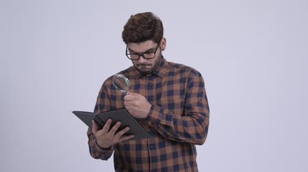 nagyító : Happy young bearded Indian hipster man reading book with magnifying glass