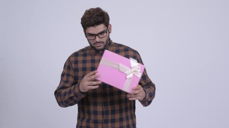 Happy young bearded Indian hipster man shaking gift box