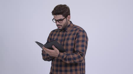Happy young bearded Indian hipster man reading book