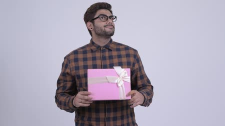 Happy young bearded Indian hipster man holding gift box and thinking