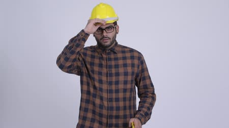 Happy young bearded Indian man construction worker giving hardhat