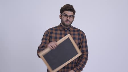 Happy young bearded Indian hipster man holding blackboard and giving thumbs up